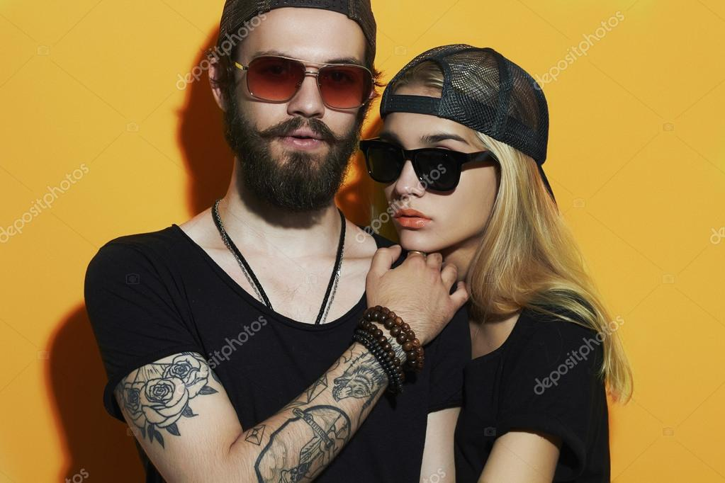 fashion beautiful couple together. Tattoo Hipster boy and girl. Bearded young man and blonde in sunglasses