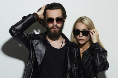 gorgeous fashion beautiful couple in black clothes wearing trendy glasses together. Hipster boy and girl. Bearded young man and blonde in sunglasses