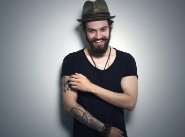 young bearded man. Smiling Hipster boy.handsome man in hat.Brutal bearded boy with tattoo