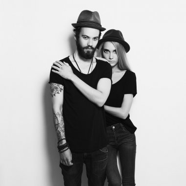fashion beautiful couple in hat together. Hipster boy and girl. Bearded young man and blonde. Tattoo