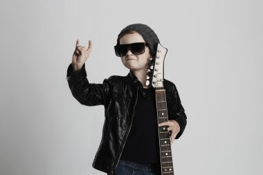 Funny rock child with guitar.little boy in sunglasses