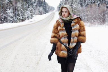 beautiful girl in a fur coat waiting for the car on a winter road in the forest.young Woman in fashionable Fur Coat,leather gloves and scarf