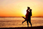 Fotografie Romantic couple on the beach at colorful sunset on background