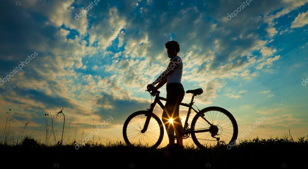 Biker at the sunset on the meadow