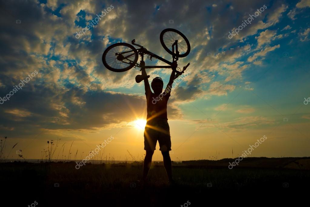 Biker holds bike high up in the sky