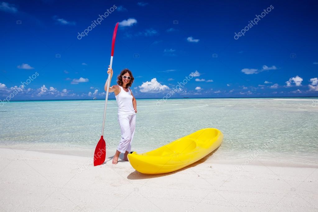 Young caucasian woman keeps paddle at the seashore near yellow k