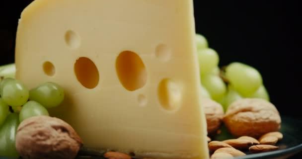 Detailní část středního tvrdého sýra hlava edam gouda parmezán na dřevěné desce, s ořechy a hrozny hniloby na talíři.