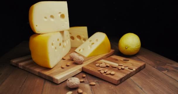 Střední tvrdá sýrová hlava edam gouda parmezán na dřevěné desce, s ořechy a medem. Snímek.