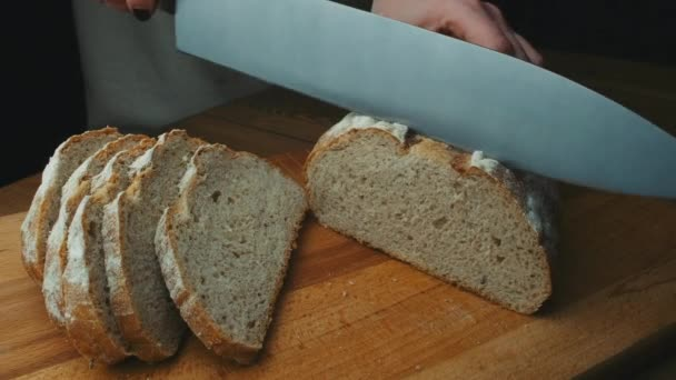 Woman cutting bread at the kitchen. Slicing bread to make a sandwich. Cooking process