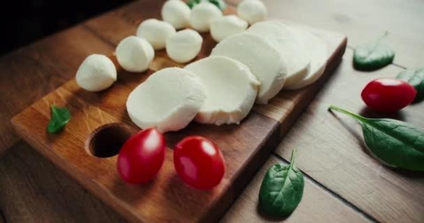 Bílé malé mozzarella sýrové kuličky, špenátové listy na dřevěné desce. Dolly-in shot.
