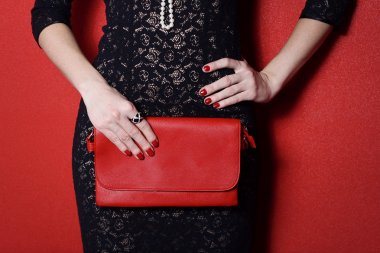 Fashionable woman with a red bag in her hands