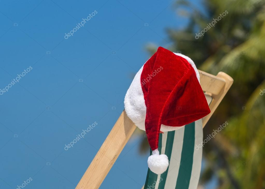 Sun lounger with Santa hat at beautiful tropical beach with whit