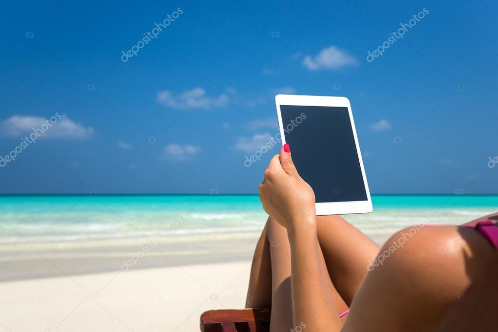 Blank empty tablet computer in the hands of women on the beach