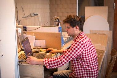 Carpenter worker prepares a computer program software for CNC ma