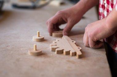 portrait  hands carpenter   wood element wheel dinosaur toy  at