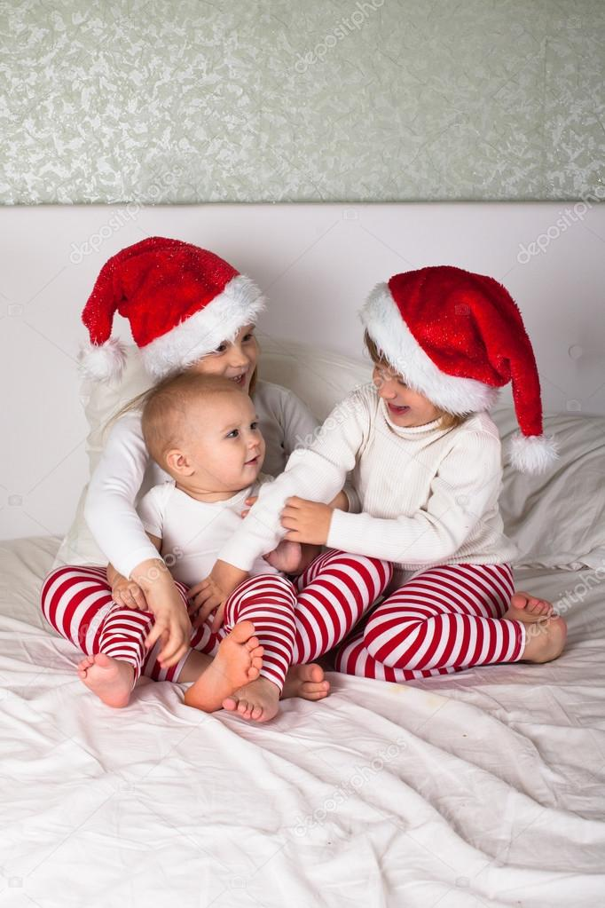 5b079e25e2 Niños graciosos en sus pijamas y gorras de Navidad en la cama