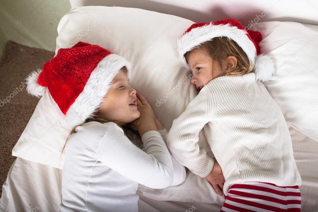 746be76ccb Niños graciosos en sus pijamas y gorras de Navidad en la cama — Foto de  Stock