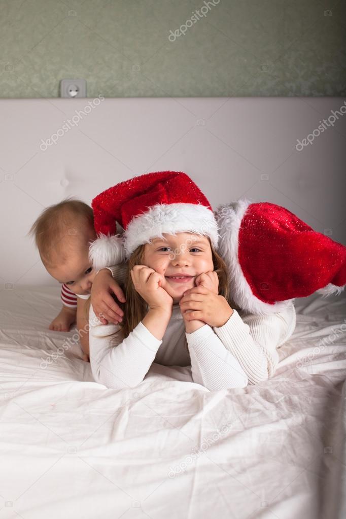 fee713fd76 Niños graciosos en sus pijamas y gorras de Navidad en la cama — Fotos de  Stock