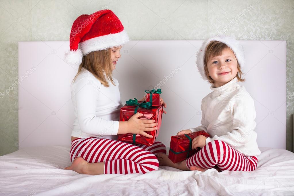 lustige Kinder in ihren Pyjamas und Weihnachten Kappen auf dem Bett ...