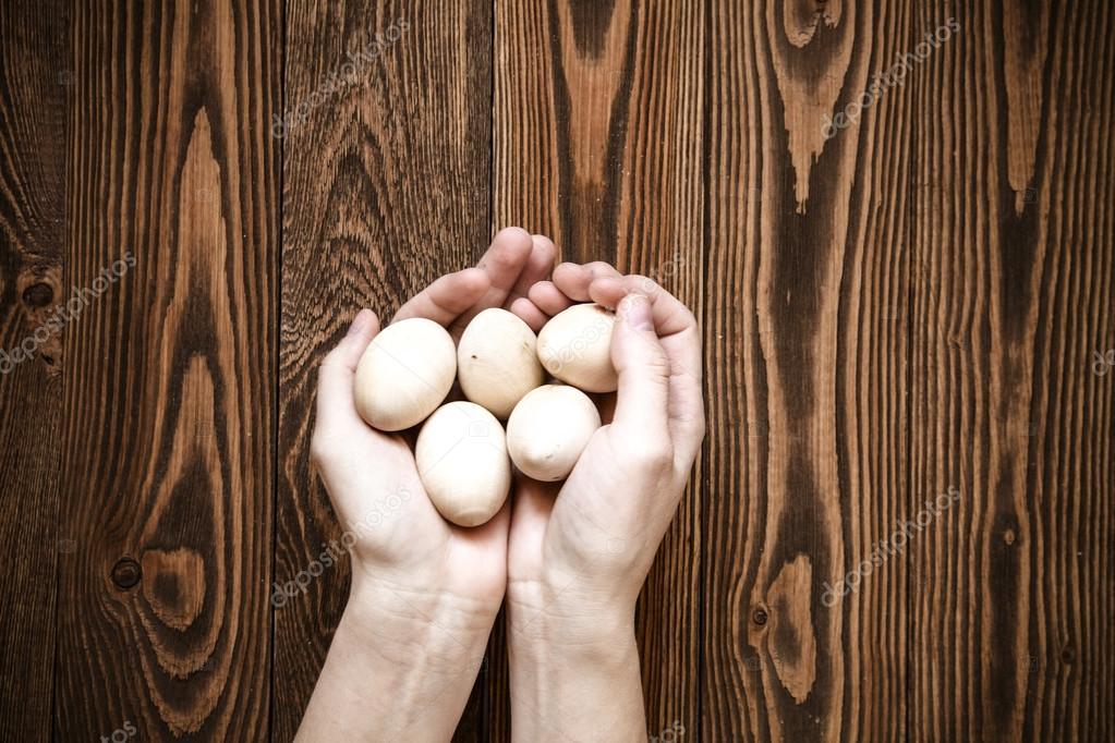Handvoll Holz Spielzeug Eier, Hände, braun-Holz-Hintergrund ...