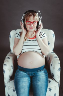 pregnant woman listening to music on headphones