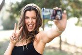 Gyönyörű fiatal nő selfie a parkban