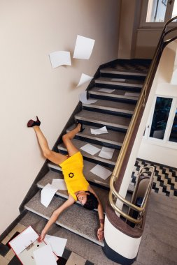 Woman with documents falls down the stairs