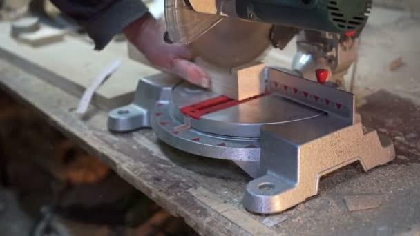 Carpenter je řezání dřevěný bar s elektrická řetězová pila