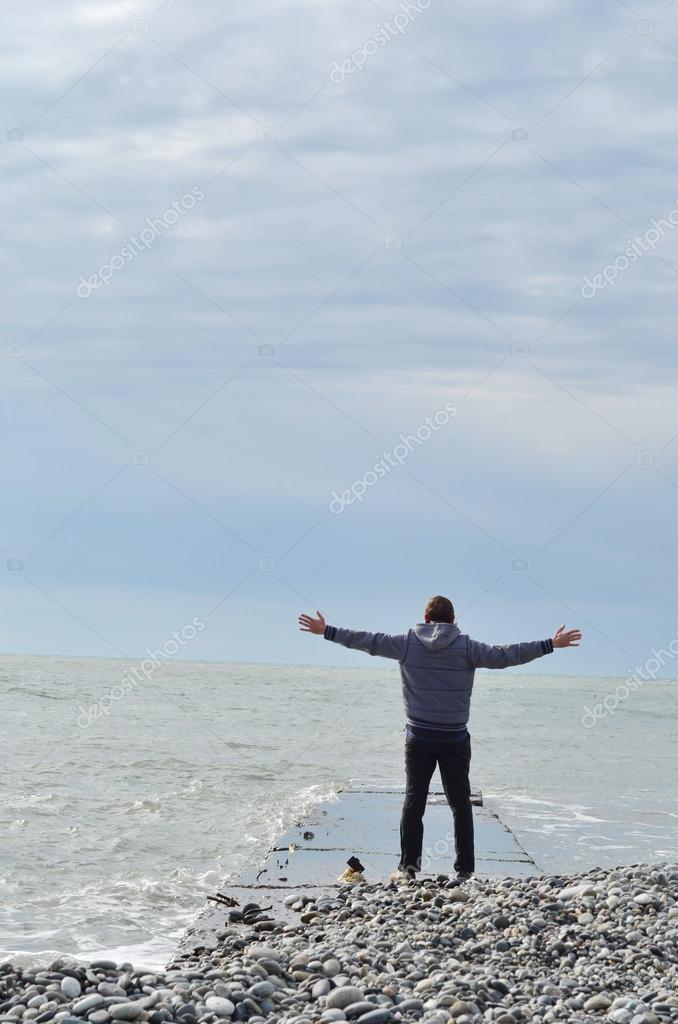 Man standing on pier looking at the sea