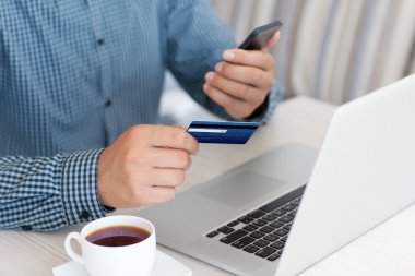 man makes the payment by credit card on the laptop