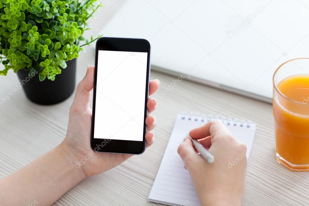 Women hand holding the phone and writing in a notebook