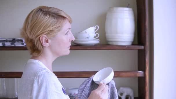 Žena zamyšleně utře nádobí a položí je na starobylou dřevěnou polici.