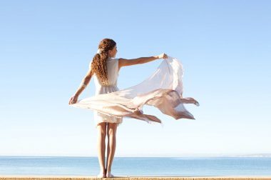 Woman in white against sky and sea