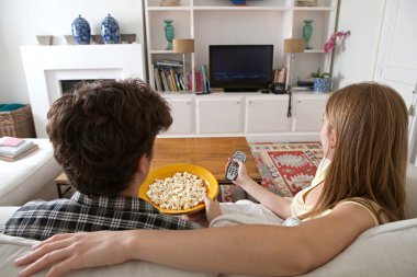 Couple watching television, eating pop corn