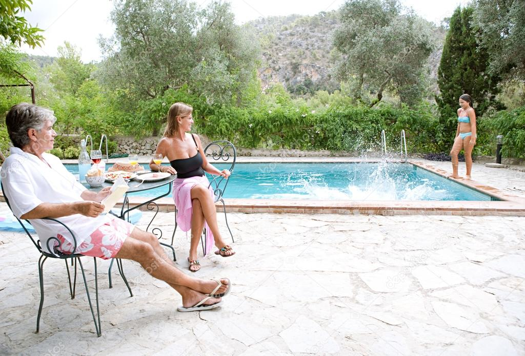 family in a holiday home garden with a swimming pool