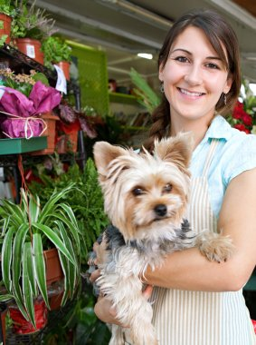 florist woman holding a dog in her store