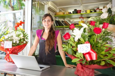 florist woman using a laptop in her store