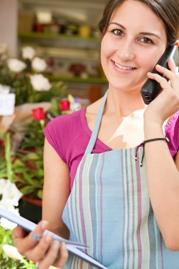 florist woman using the phone with a clipbard in her store