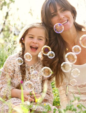 mother and daughter playing to blow floating bubbles