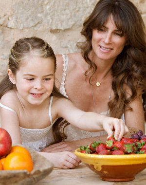 mother and daughter eating fruits at table