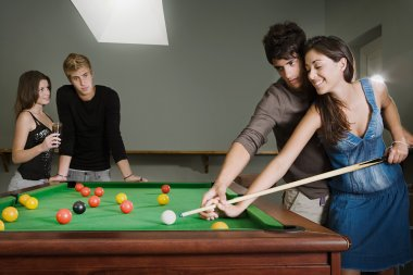 couples playing pool together in a bar