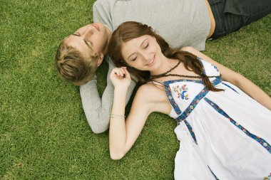 couple laying down on green grass in a park