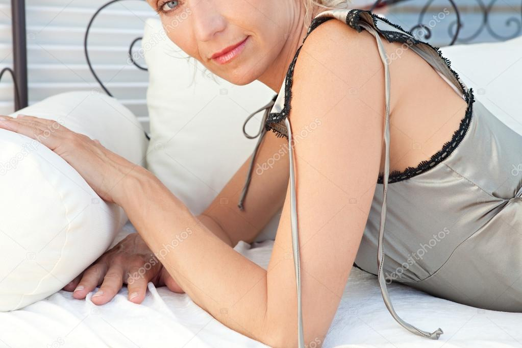 Woman lounging on a bed on a terrace outdoors