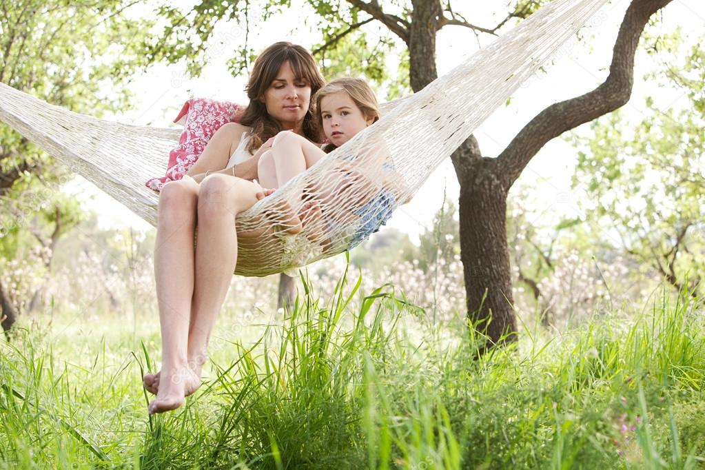 mother and daughter together in a hammock in a home garden