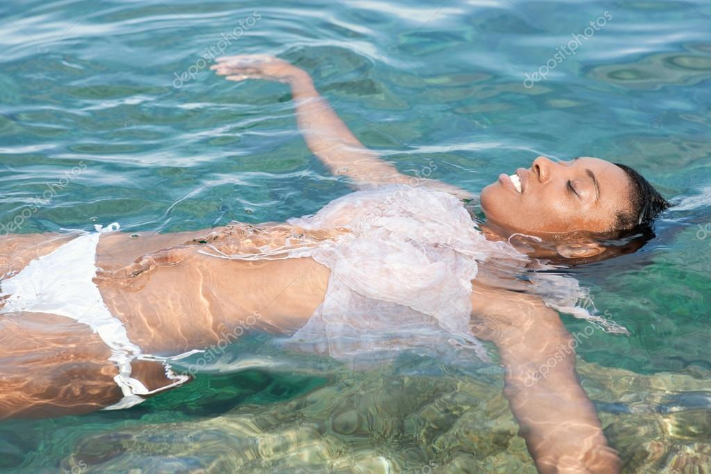 Black woman swimming and floating in the sea