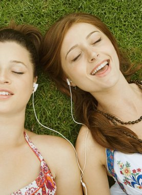 girls listening to music on green grass