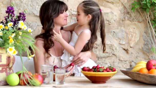 mother and daughter eating fruits outdoors