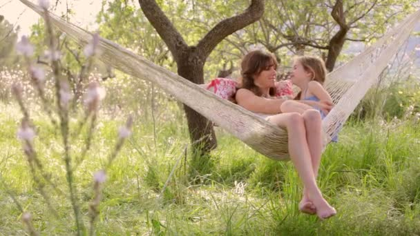 mother and daughter sitting together in a hammock