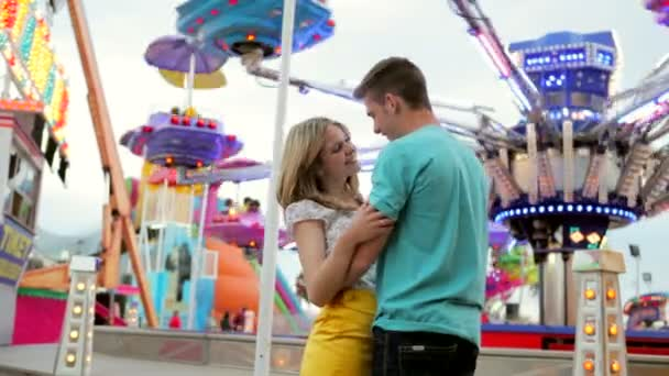 couple hugging and kissing in an attractions park