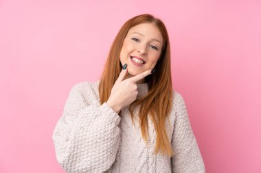 Young redhead woman over isolated pink background smiling